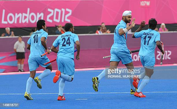 Teammates run towards Sandeep Singh of India as he celebrates after scoring a goal against New Zealand during the men's field hockey preliminary...