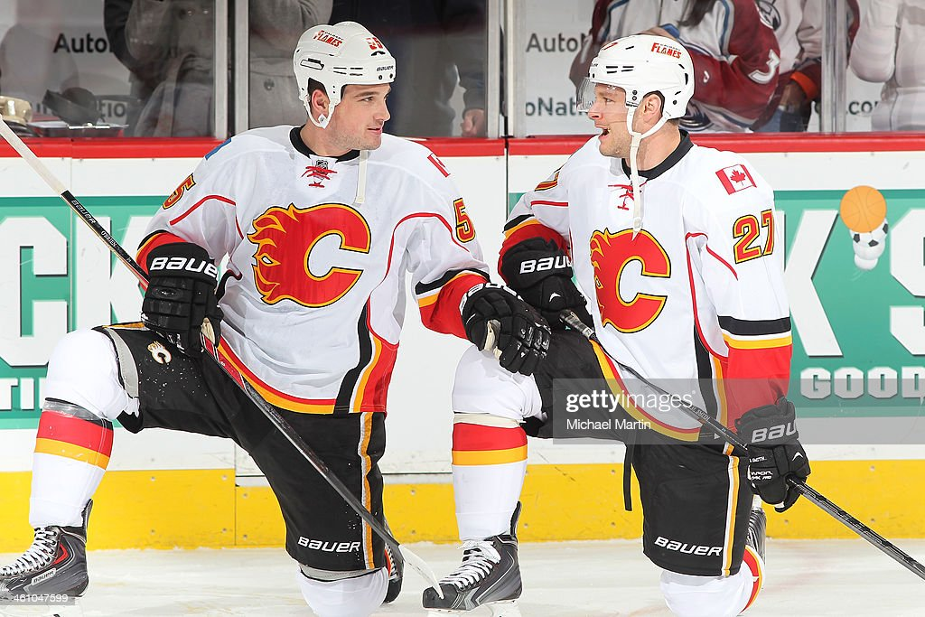 Teammates Shane O'Brien #55 and Derek Smith #27 of the Calgary Flames talk prior to the game against the Colorado Avalanche at the Pepsi Center on January 06, 2014 in Denver, Colorado.