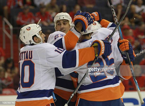 Teammates surround Nino Niederreiter of the New York Islanders following his first NHL career goal against the Washington Capitals at the Verizon...