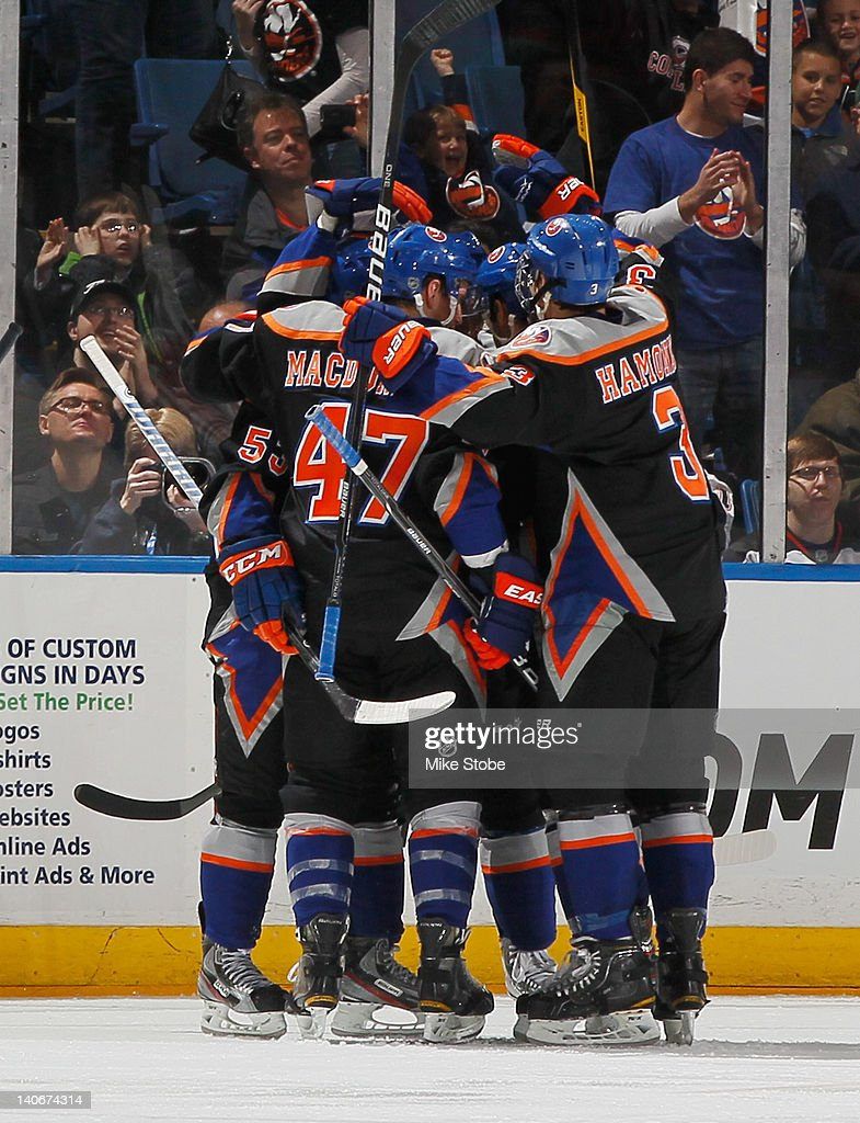 Teammates swarm <a gi-track='captionPersonalityLinkClicked' href=/galleries/search?phrase=Kyle+Okposo&family=editorial&specificpeople=540469 ng-click='$event.stopPropagation()'>Kyle Okposo</a> #21 of the New York Islanders after his second period goal against the New Jersey Devils at Nassau Veterans Memorial Coliseum on March 4, 2012 in Uniondale, New York.