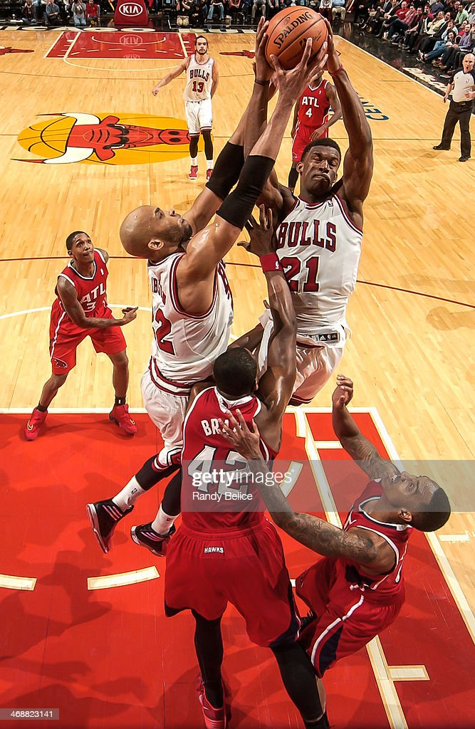 Teammates Taj Gibson #22 and Jimmy Butler #21 of the Chicago Bulls jump for the rebound against Elton Brand #42 of the Atlanta Hawks on February 11, 2013 at the United Center in Chicago, Illinois.
