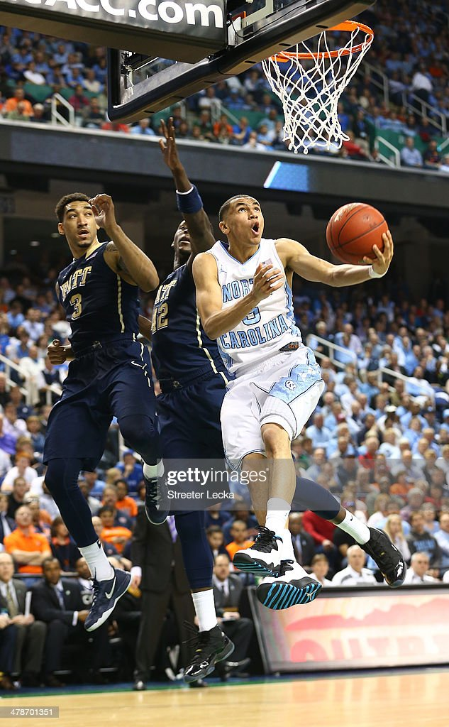 Teammates Talib Zanna and Cameron Wright of the Pittsburgh Panthers watch as Marcus Paige of the North Carolina Tar Heels drives to the basket during...