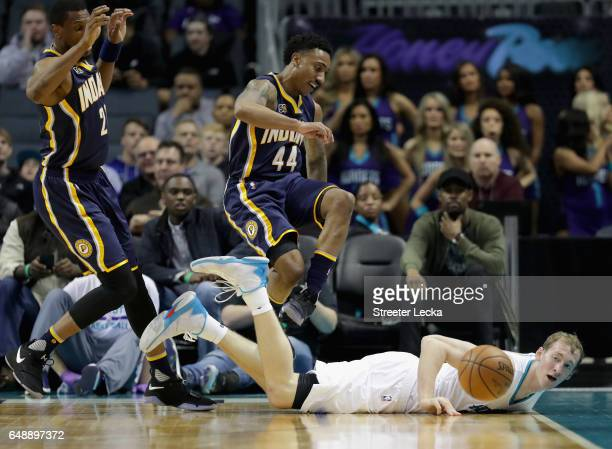 Teammates Thaddeus Young and Jeff Teague of the Indiana Pacers scramble for a loose ball against Cody Zeller of the Charlotte Hornets during their...