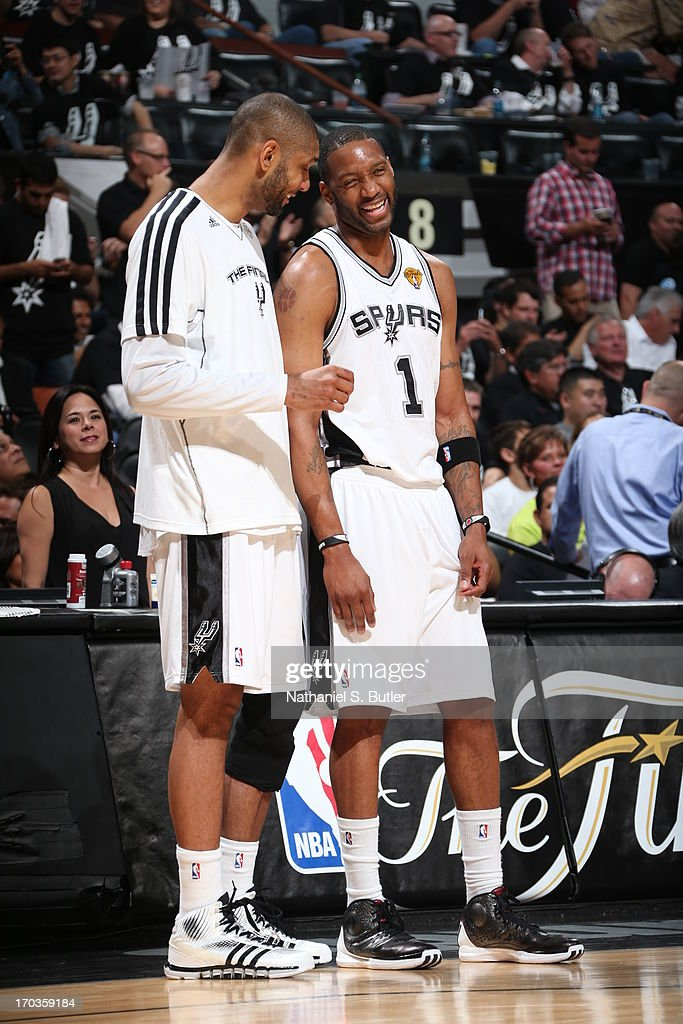 Teammates Tim Duncan #21 and Tracy McGrady #1 of the San Antonio Spurs while playing against the Miami Heat in Game Three of the 2013 NBA Finals on June 11, 2013 at the AT&T Center in San Antonio, Texas.