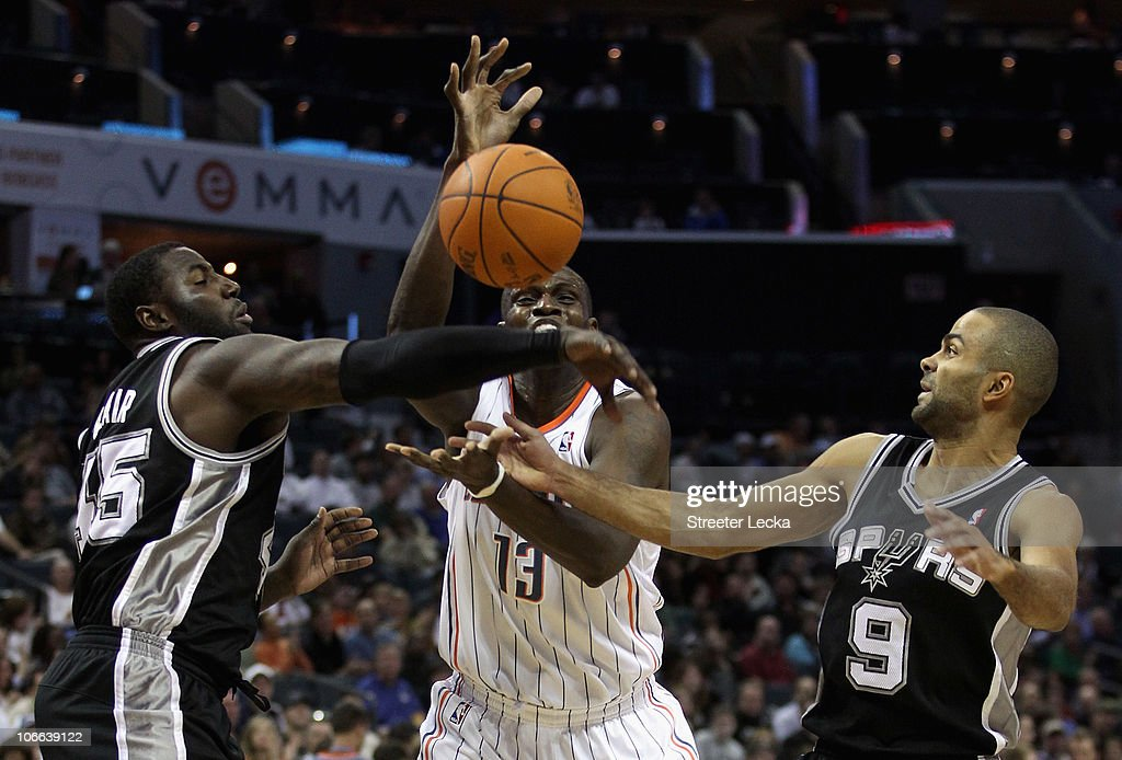 Teammates Tony Parker #9 and <a gi-track='captionPersonalityLinkClicked' href=/galleries/search?phrase=DeJuan+Blair&family=editorial&specificpeople=4649451 ng-click='$event.stopPropagation()'>DeJuan Blair</a> #45 of the San Antonio Spurs battle for a loose ball with <a gi-track='captionPersonalityLinkClicked' href=/galleries/search?phrase=Nazr+Mohammed&family=editorial&specificpeople=201690 ng-click='$event.stopPropagation()'>Nazr Mohammed</a> #13 of the Charlotte Bobcats during their game at Time Warner Cable Arena on November 8, 2010 in Charlotte, North Carolina.
