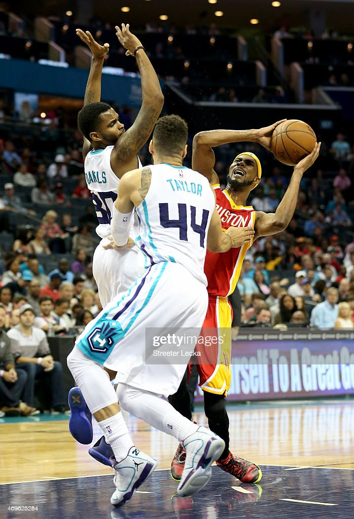 Teammates Troy Daniels and Jeff Taylor of the Charlotte Hornets try to stop Corey Brewer of the Houston Rockets during their game at Time Warner...