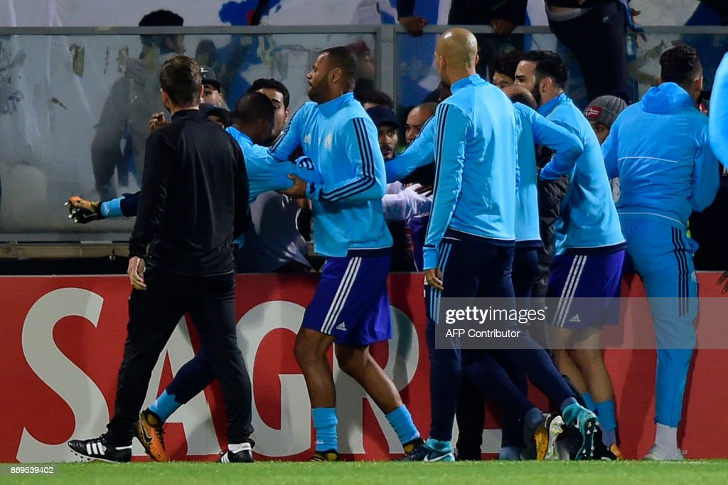 TOPSHOT - Teammates try to calm down Marseille's defender Patrice Evra (back L) as he tries to kick a supporter before the start of the UEFA Europa League group I football match Vitoria SC vs Marseille at the D. Afonso Henriques stadium in Guimaraes on November 2, 2017. /