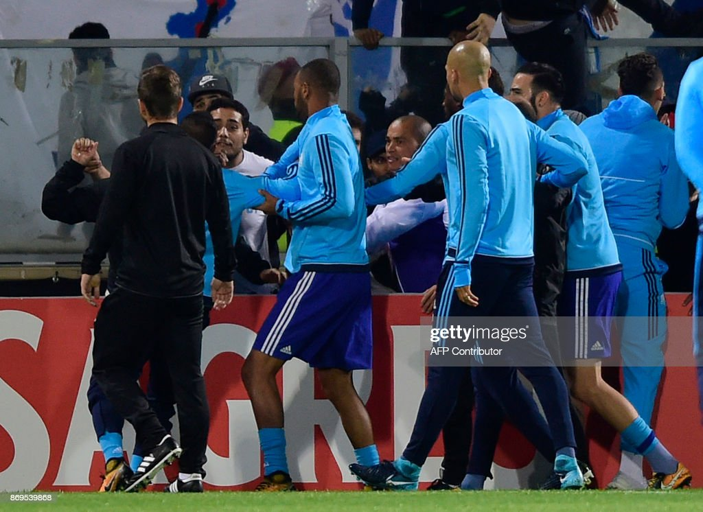 Teammates try to calm down Marseille's French defender Patrice Evra (back-L) as he argues with supporters before the start of the UEFA Europa League group I football match Vitoria SC vs Marseille at the D. Afonso Henriques stadium in Guimaraes on November 2, 2017. /