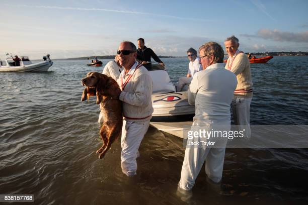 Teams leave by boat after playing a cricket match on the Brambles sandbank at low tide on August 24 2017 in Hamble England The annual event sees...