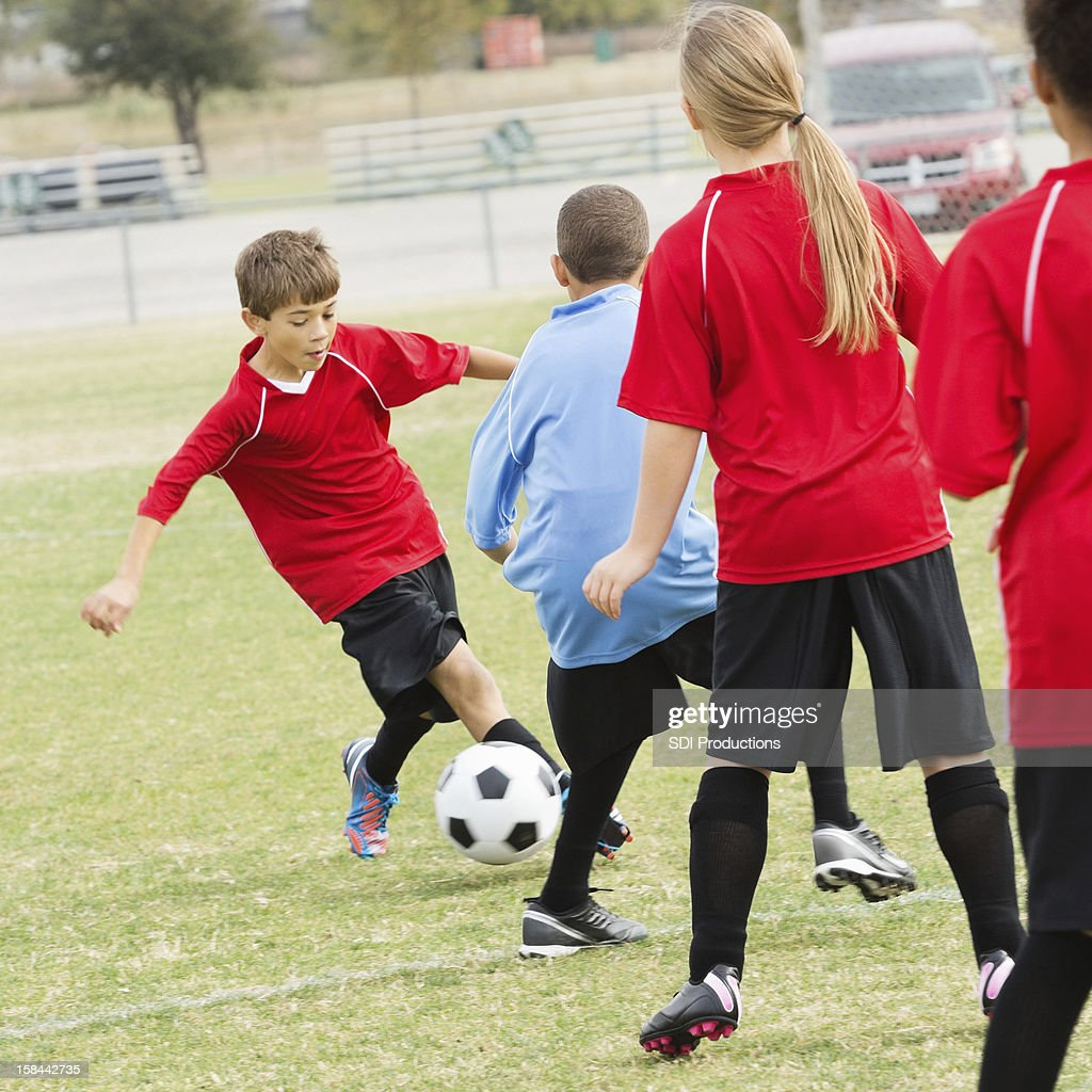 Teams of children playing in outdoor soccer game : Stock Photo