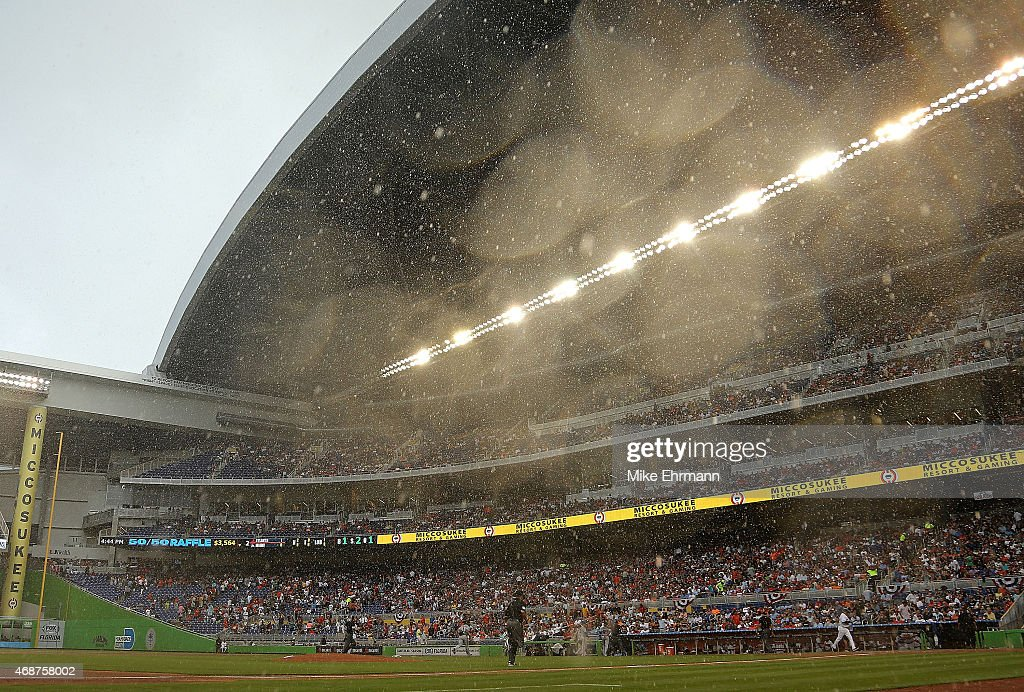 Teams retreat to the dugout during a rain delay at Marlins Park during Opening Day between the Miami Marlins and the Atlanta Braves on April 6 2015...