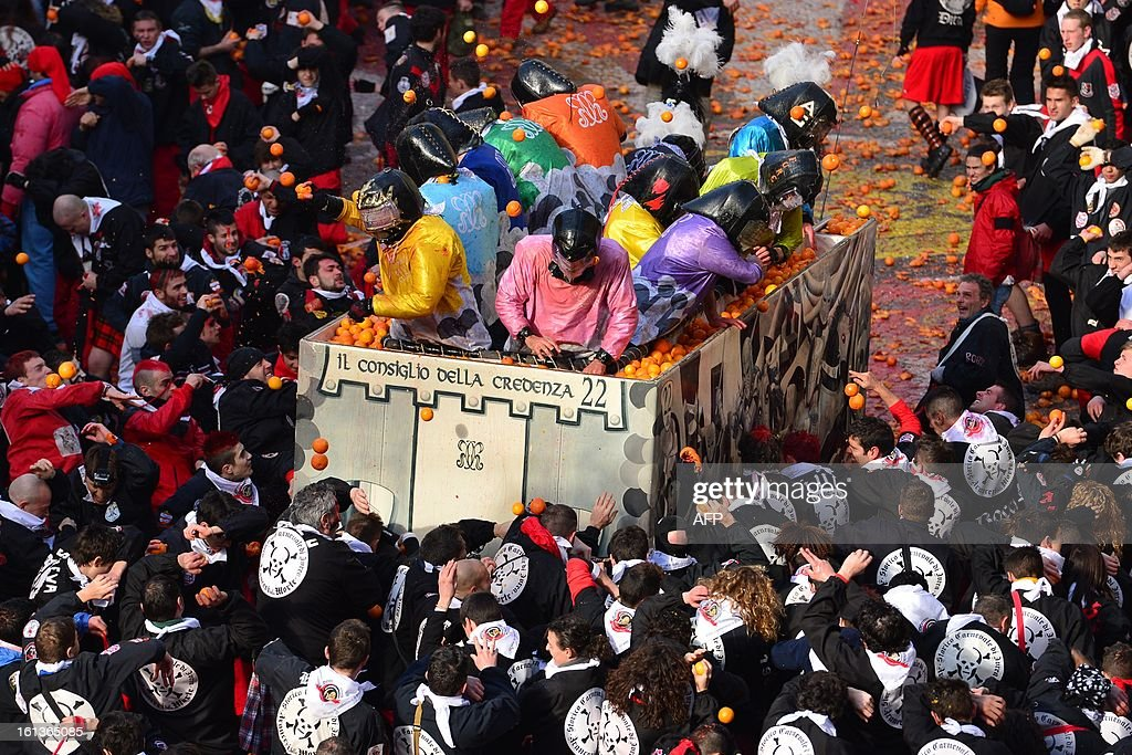 Teams throw oranges at each other during the traditional 'battle of the oranges' held during the carnival in Ivrea, near Turin, on February 10, 2013. During the event which marks the people's rebellion against tyrannical lords who ruled the town in the Middle Ages, revellers parading on floats represent guards of the tyrant, while those on foot the townsfolk.