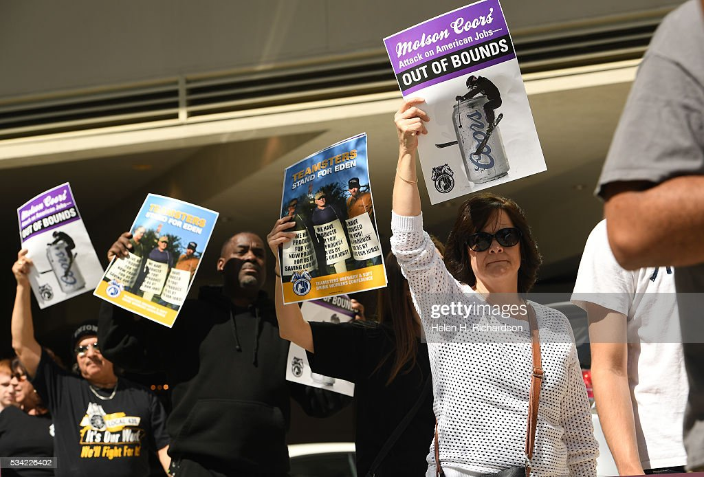Teamsters Cindy Gallegos, in white, Marc Dennis second from left, and Jesse Medina, in back join others as they hold signs to protest Molson Coors' annual shareholder meeting outside at 1881 Curtis street in Denver, Colorado on May 25, 2016 in Denver, Colorado. The protestors wanted to raise concerns about the planned closure of the award-winning MillerCoors brewery in Eden, N.C. The closure will impact 450 Teamster families in that state. The decision to close Eden was announced on September 14, just two days before the merger talks between SABMiller (LON: SAB) and AB/Inbev (NYSE: BUD) were formally disclosed to the public. Teamsters will warn shareholders of the likely anticompetitive effects of that decision and how it may be viewed by regulators.