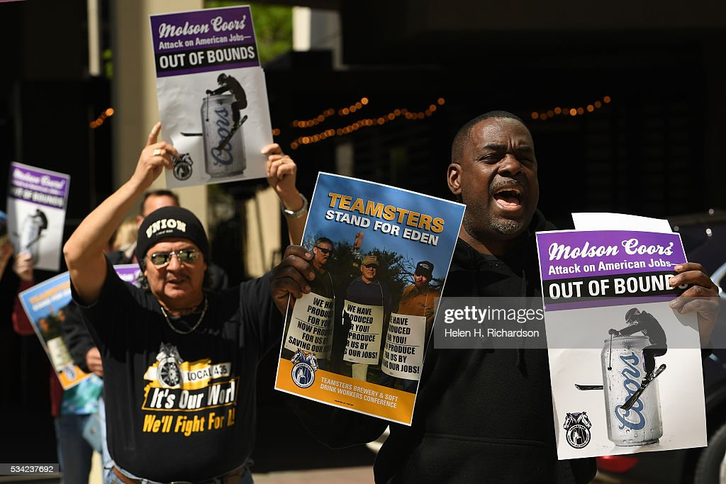 Teamsters Marc Dennis, right, and Jesse Medina, in back, join others as they hold signs to protest Molson Coors' annual shareholder meeting outside at 1881 Curtis street in Denver, Colorado on May 25, 2016 in Denver, Colorado. The protestors wanted to raise concerns about the planned closure of the award-winning MillerCoors brewery in Eden, N.C. The closure will impact 450 Teamster families in that state. The decision to close Eden was announced on September 14, just two days before the merger talks between SABMiller (LON: SAB) and AB/Inbev (NYSE: BUD) were formally disclosed to the public. Teamsters will warn shareholders of the likely anticompetitive effects of that decision and how it may be viewed by regulators.