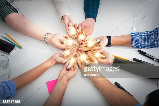 Teamwork and brainstorming concept with businessmen that share an idea with a lamp. Concept of startup : Foto stock