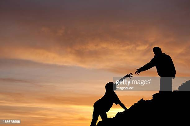 Teamwork Concept of Boy Assisting Another Silhouette