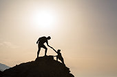 Teamwork couple helping hand trust silhouette in inspiring mountains. Team of climbers assistance man and woman hiker, help each other on top of mountain, beautiful sunrise landscape in Crete Greece