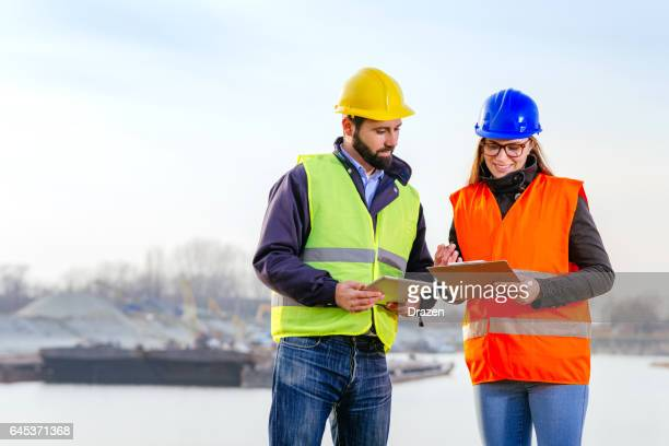Teamwork in freight transportation industry - two engineers working together at the dock