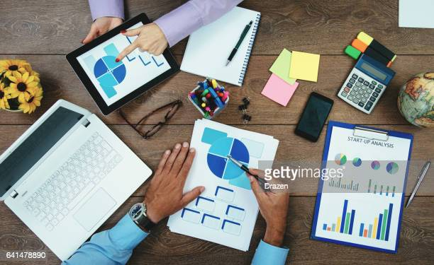 Teamwork in office - man and woman dealing with financial data, taxation and stock markets