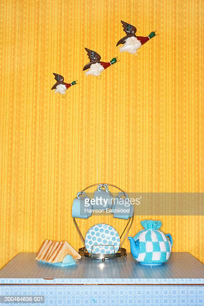 Teapot and breakfast set on table, flying ducks on wall in background