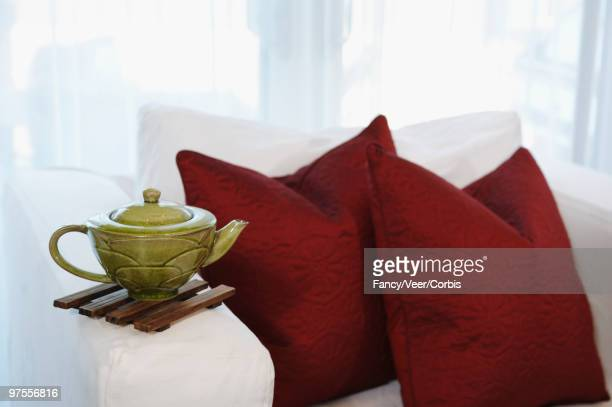 Teapot balanced on arm of upholstered chair