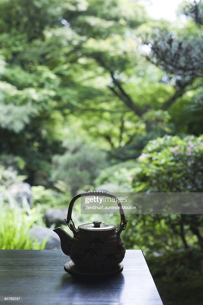 Teapot resting on table, Japanese scenery in background : Stock Photo