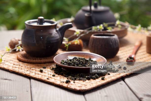 Teapot, tea whisk and bowl of dried green tea leaves lying on tray, China