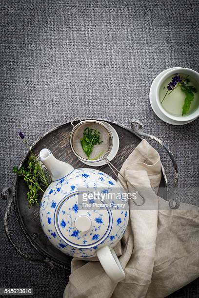 Teapot with blue floral pattern on vintage tray with linnen napkin on grey fabric. Top view