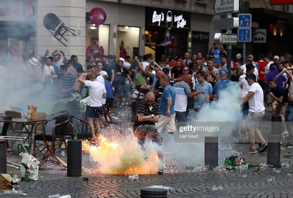 A tear gas canister explodes under a football fan as England fans clash with police in Marseille on June 10 2016 in Marseille France Football fans...
