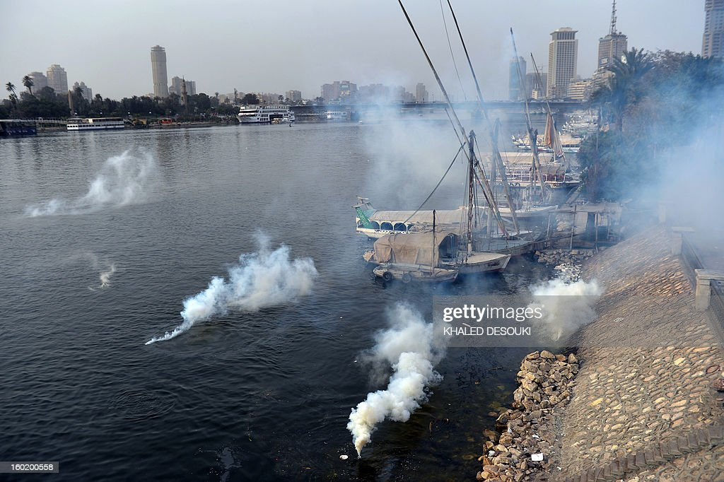 Tear gas canisters fired by Egyptian riot police land in the waters of the river Nile during clashes near Cairo's Tahrir Square, on January 27, 2013. Clashes killed at least 31 people in Egypt's Port Said as violence raged into the early hours in several cities including the capital following death sentences passed on 21 football fans after a riot.