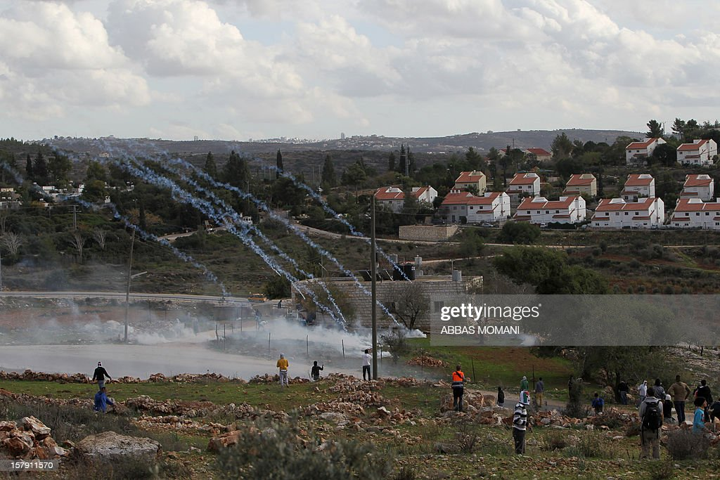 Tear gas canisters fired by Israeli soldiers land next to Palestinian protesters during clashes following a demonstration against the expropriation of Palestinian land by Israel in the West Bank village of Nabi Saleh on December 7, 2012.