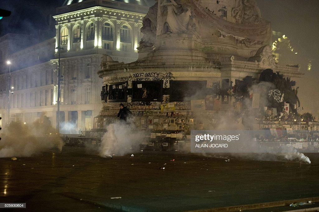 Tear gas cannisters explode their content as police clear the Place de la Republique in Paris during a protest by the Nuit Debout, or 'Up All Night' movement who have been rallying against the French government's proposed labour reforms on April 29, 2016. People were arrested and others detained during the overnight clashes in the French capital as the police dispersed the protesters whose movement began on March 31 in opposition to the government's proposed labour reforms. / AFP / ALAIN