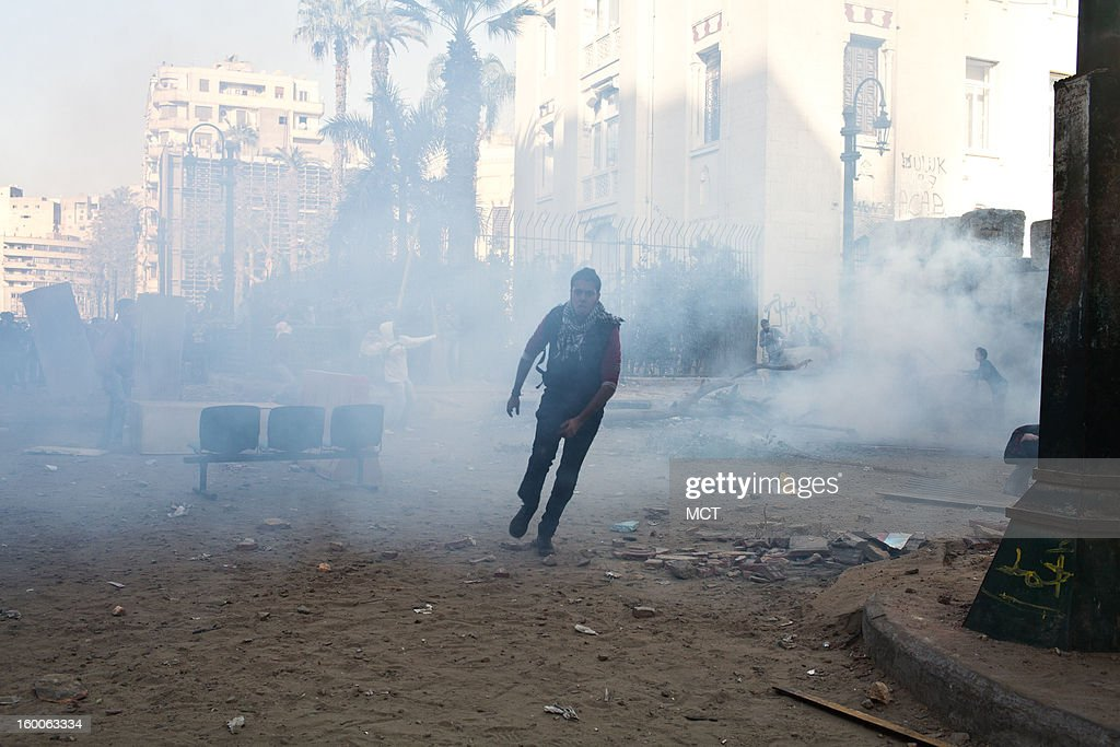 Tear gas fills the air as protesters attempt to take down part of a wall on Qasr el Aini street during Friday's gathering for the anniversary of the revolution. Tens of thousands of Egyptians protested Friday, January 25, 2013 in Tahrir Square in Cairo, Egypt, against the Islamist-led government's failure to fix the economy and heal the politically divided nation two years after the overthrow of Hosni Mubarak.