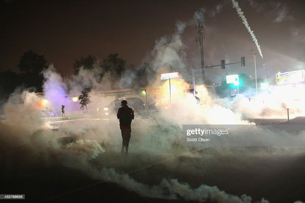 Tear gas fills the street as a demonstrator walks through the haze during protests over the killing of teenager Michael Brown by a Ferguson police officer, on August 17, 2014 in Ferguson, Missouri. Despite the Brown family's continued call for peaceful demonstrations, violent protests have erupted nearly every night in Ferguson since his August 9, death.