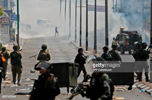 TOPSHOT Tear gas fumes billow during clashes between Palestinian protesters and Israeli forces after Friday prayers at the main entrance of the West...