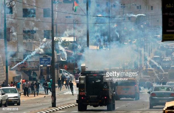 Tear gas fumes billow during clashes between Palestinian protesters and Israeli forces after Friday prayers at the main entrance of the West bank...