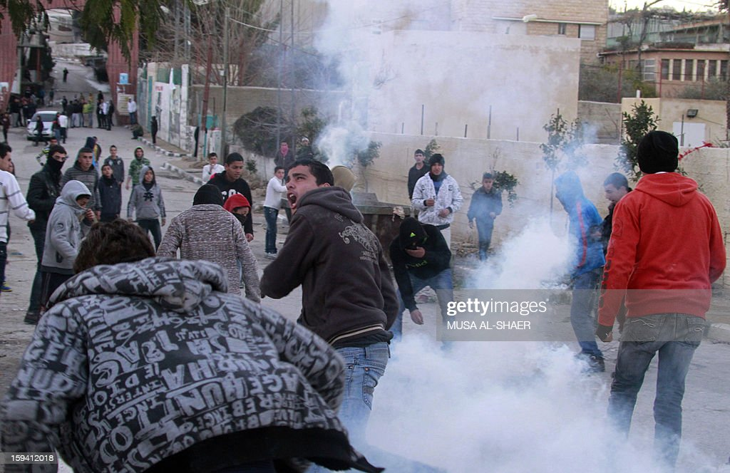 Tear gas is fired as Palestinian protesters throw stones at an Israeli military observer tower during a protest in the Aida Palestinian refugee camp near the West Bank city of Bethlehem on January 13, 2013. Earlier, some 500 Israeli police moved to evacuate the West Bank Palestinian protest camp of Bab al-Shams, a tent village activists set up on January 11, in the controversial E1 area outside Jerusalem, several kilometers from Bethlehem.