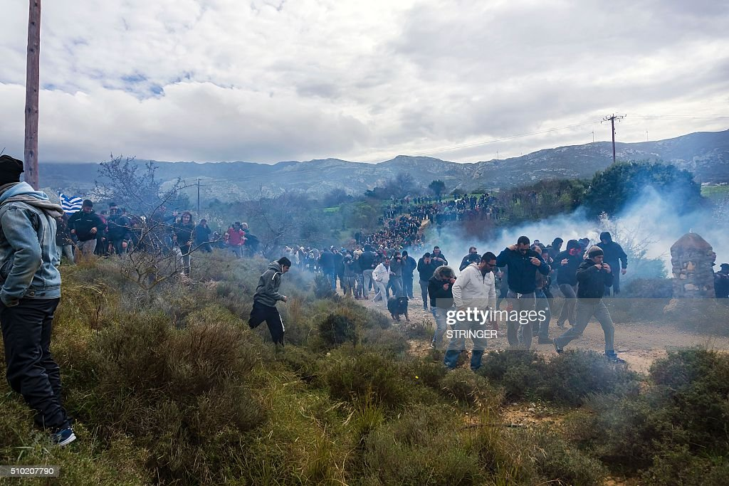 Tear gas is fired as people protest against the so-called 'hotspot' being built for refugees and migrants on the Aegean island of Kos, on February 14, 2015. Greek riot police fired tear gas at demonstrators protesting against the development of a centre to house migrants on the tourist island of Kos, media reports said. About 2,000 people joined a rally against the so-called 'hotspot' being built on the Aegean island despite the opposition of local residents and the mayor, fearful of the effect on the vital tourism industry. / AFP / Eurokinissi / STRINGER