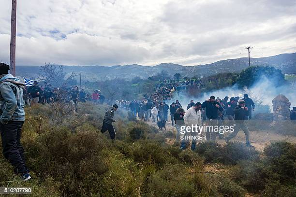 TOPSHOT Tear gas is fired as people protest against the socalled 'hotspot' being built for refugees and migrants on the Aegean island of Kos on...