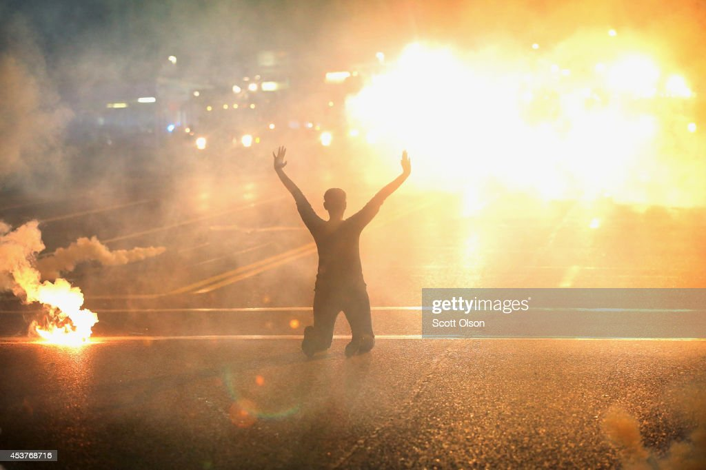 Tear gas reigns down on a woman kneeling in the street with her hands in the air after a demonstration over the killing of teenager Michael Brown by...