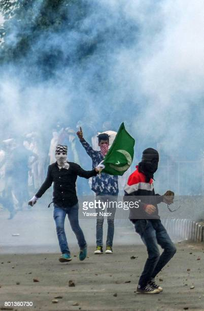 Tear gassed Kashmiri protesters hold flags and banners as they throw bricks and stones at Indian government forces during an anti India protest on...