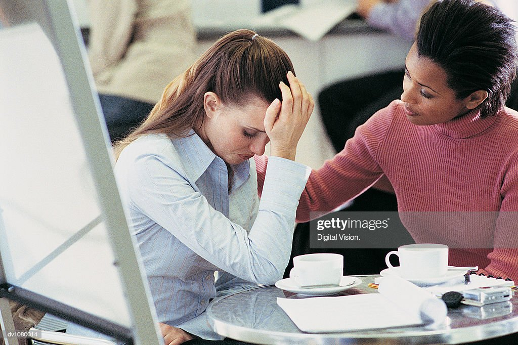 Tearful Businesswoman Being Consoled by a Colleague Sitting at a Table in an Office Canteen