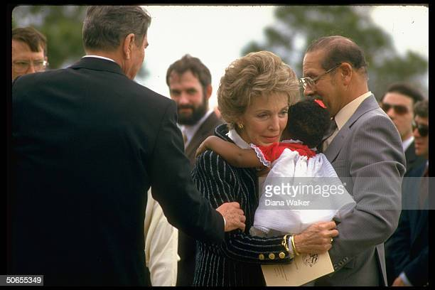 Tearful Nancy Reagan cuddling Joy McNair baby daughter of astronaut who died in fatal explosion on the space shuttle Challenger as President Ronald...