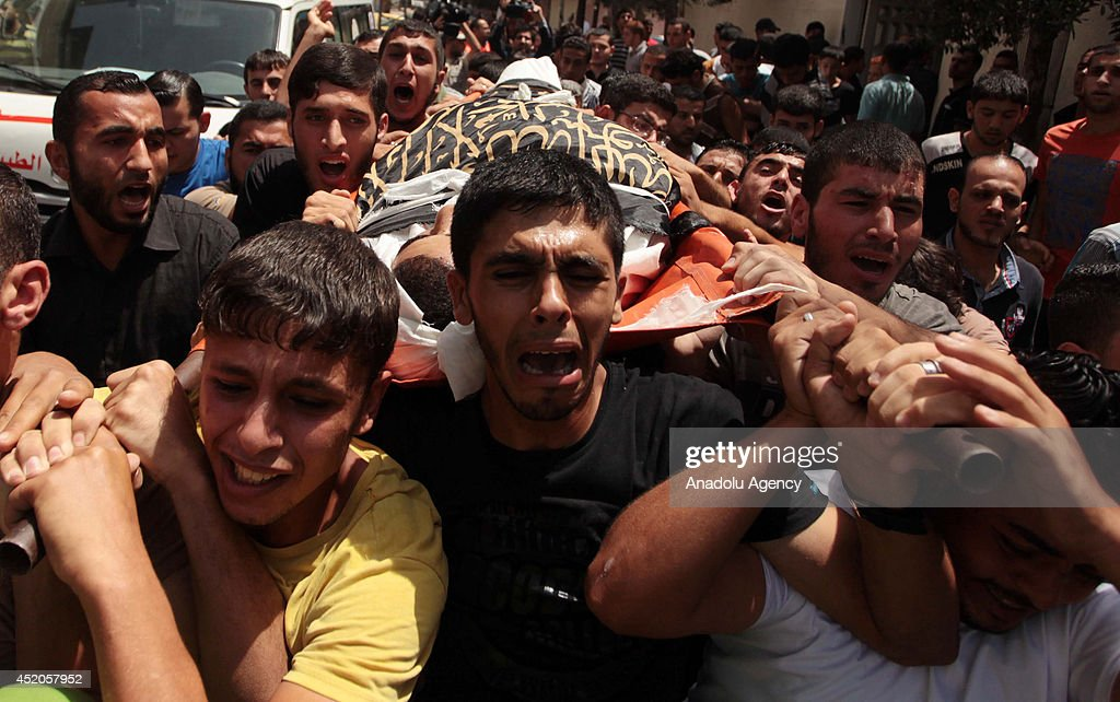 Tearful relatives of Mohammed Sweilem killed in an Israeli airstrike staged to Jabalia Refugee Camp attend the funeral ceremony on July 12 2014 in...