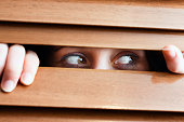 Tearful woman looks nervously sideways through venetian blind