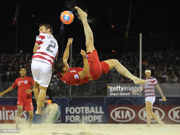 Tearii Labaste of Tahiti is challenged by Jason Leopoldo of USA during the FIFA Beach Soccer World Cup Tahiti 2013 Group A match between USA and...