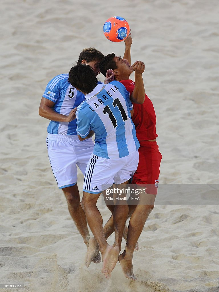Tearii Labaste of Tahiti is challenged by Luciano Franceschini and Sebastian Larreta of Argentina during the FIFA Beach Soccer World Cup Tahiti 2013 Quarter Final match between Argentina and Tahiti at the Tahua To'ata Stadium on September 25, 2013 in Papeete, French Polynesia.