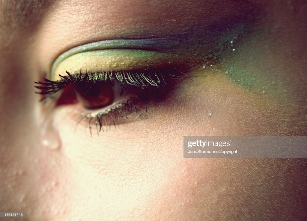 Tears in eyes of girl with colorful eye lids : Stock Photo