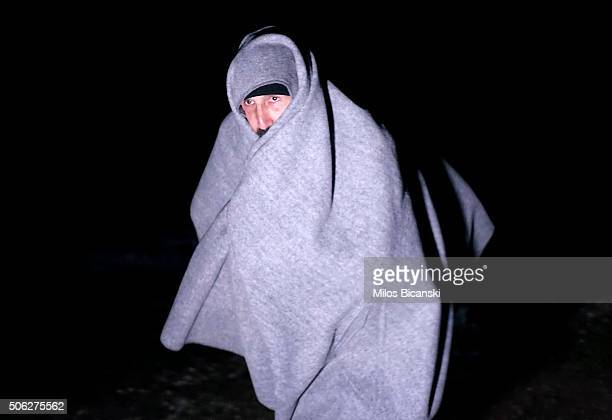 Tears roll down the cheeks of a migrant's face as he walks wrapped in a blanket after crossing the Macedonian Serbian border near to the southern...