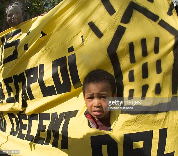 Tears run through the cheeks of this small child while he is helping to carry a sign that claims for decent jobs and housing Several thousand...